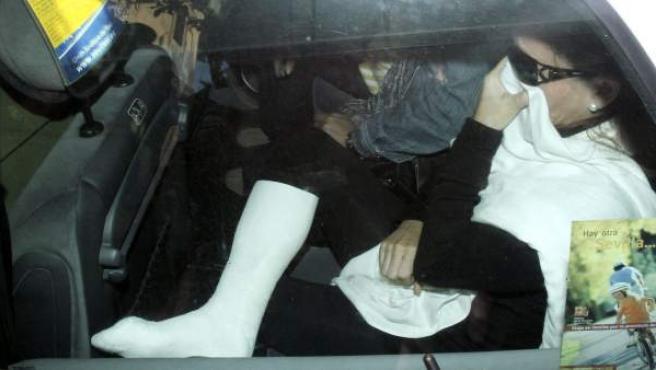 La madre del Cuco, Rosalía G.M., con la pierna derecha escayolada, a su llegada en un taxi directamente a la cochera del edifico de la Audiencia de Sevilla.