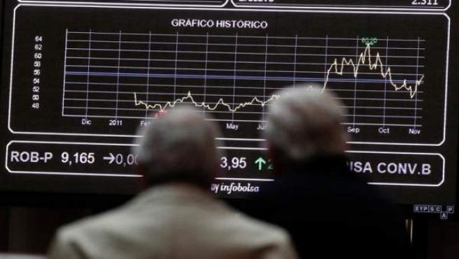 Dos personas miran la pantalla de la Bolsa de Madrid.