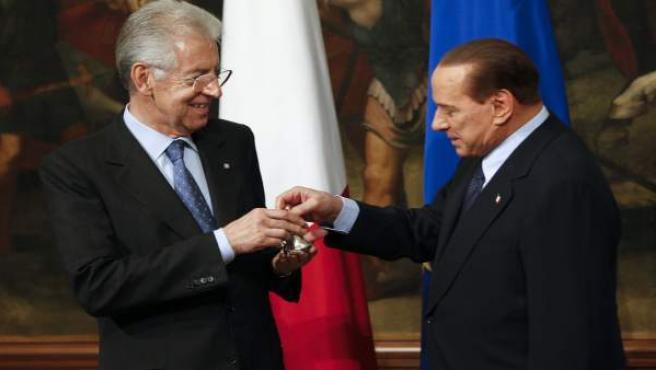 El nuevo primer ministro Mario Monti recibe de su predecesor Silvio Berlusconi una campanilla de plata como símbolo del traspaso de poderes.