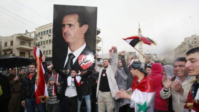 Simpatizantes del régimen de Bachar al Asad portan un cartel con su fotografía durante una manifestación para conmemorar el Día del Movimiento Correccionista, en la plaza Umayyad en Damasco (Siria).