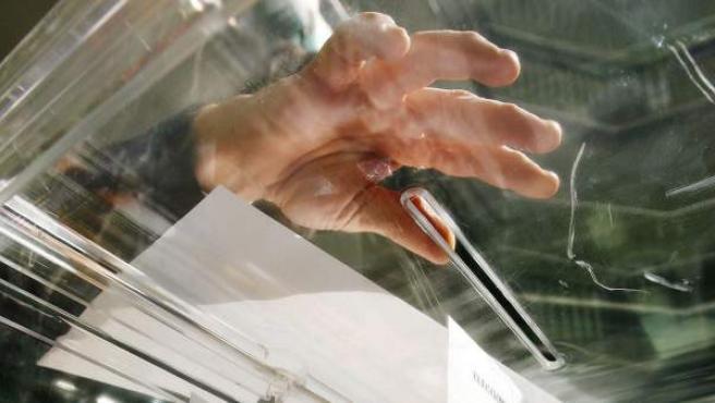 Un ciudadano deposita su voto en una urna electoral.