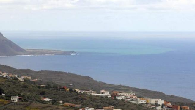 Vista del pueblo del Valle del Golfo en la que puede verse al fondo la mancha producida por la erupción volcánica submarina.