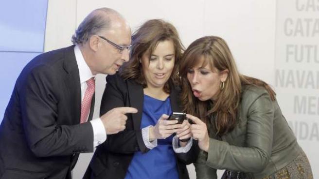 La portavoz del PP en el Congreso, Soraya Sáenz de Santamaría, muestra una fotografía a la presidenta del PPC, Alícia Sánchez Camacho y al portavoz económico, Cristóbal Montoro