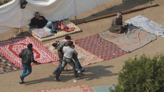 Dos manifestantes llevan al hospital a un colega herido durante la protesta convocada en la plaza Tahrir de El Cairo.