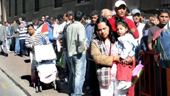 Varios inmigrantes hacen cola para regularizar su situación.
