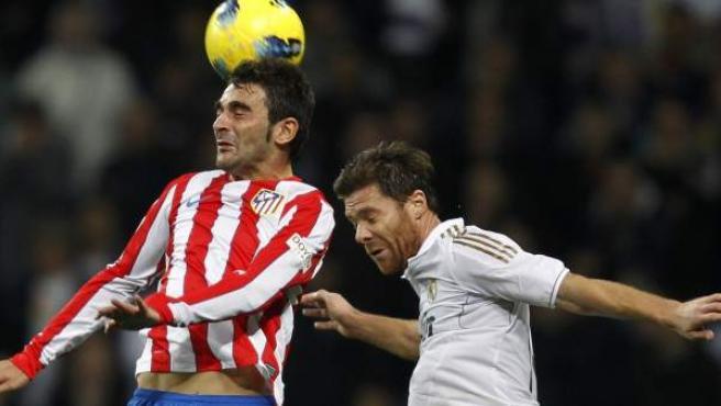 Xabi Alonso y Adrián buscan un balón aéreo durante el Real Madrid - Atlético.