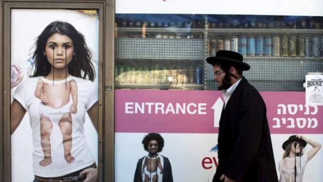 Un judio ultraortodoxo pasa frente a carteles publicitarios con pintadas en Jerusalén, Israel.