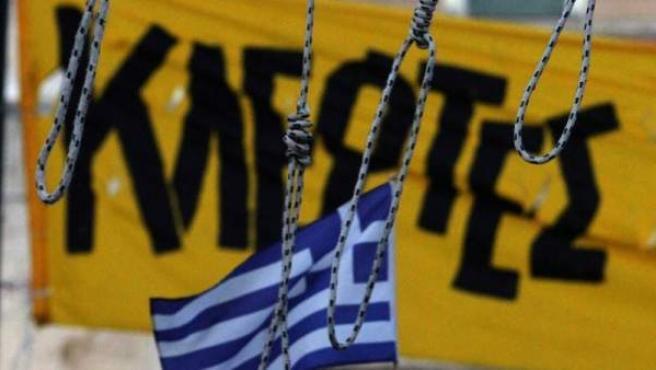 """Cuatro cuerdas de horcas frente a una bandera griega y una pancarta que dice """"ladrones"""", durante una protesta en la plaza Syntagma, junto al edificio del Parlamento en Atenas, Grecia."""