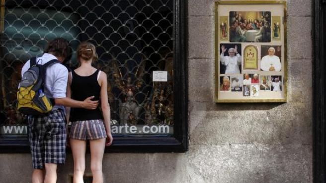 Una pareja de jóvenes mira un escaparate religioso.