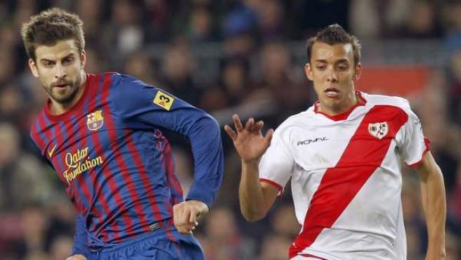 El defensa del F. C. Barcelona, Gerad Pique(i), golpea el balón ante el defensa brasileño del Rayo Vallecano, Pedro Roberto Botelho.
