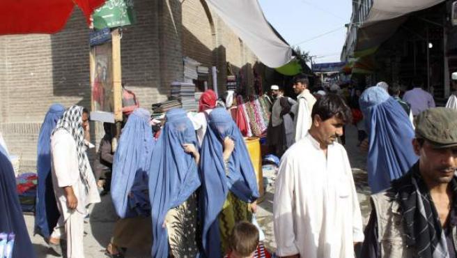 Fotografía tomada el pasado mes de julio en Kabul, en la que varias mujeres, vestidas con el tradicional burka azul, pasean por las calles de un mercado de la zona vieja de la capital afgana.