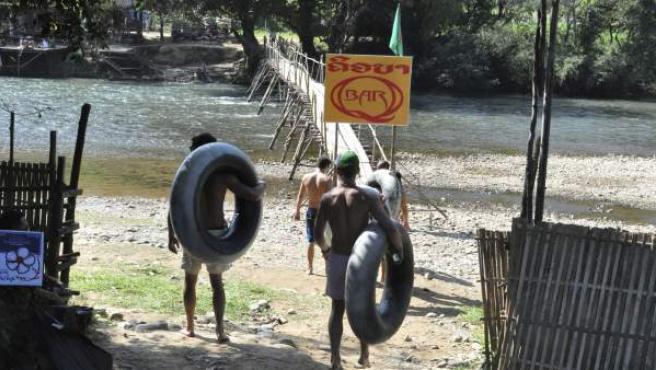 Jóvenes aventureros provistos de neumáticos se dirigen al río Nong, en Laos, para practicar 'tubing'.
