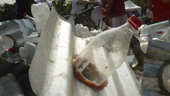 Unos voluntarios reparten bombillas ecológicas, hechas con botellas de plástico llenas de agua y lejía, que van adheridas a unas láminas de zinc, para ser ser colocadas en los tejados de las chabolas de Manila a fin de que tengan iluminación.