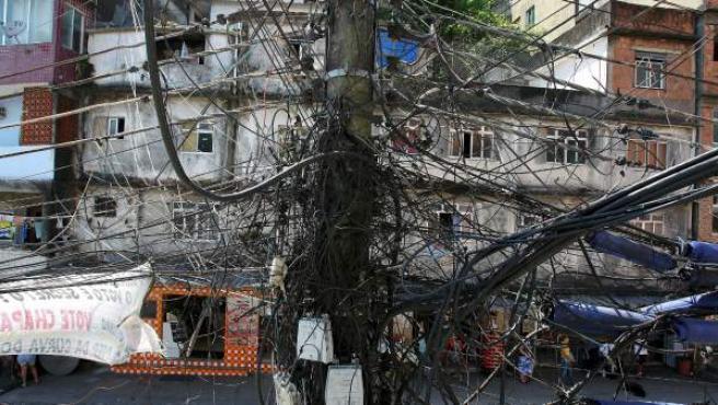 La regularización del suministro de electricidad todavía no ha comenzado en la Rocinha y las densas marañas de cables con conexiones clandestinas continúan formando parte del paisaje del barrio, al igual que en la mayoría de las favelas de Río.