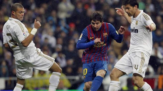Leo Messi pasa el balón ante Xabi Alonso y Pepe durante el Real Madrid - Barça.