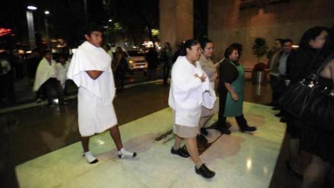 Varias personas caminan en una zona de Ciudad de México tras registrarse un seísmo que sacudió el sur y el centro de México.