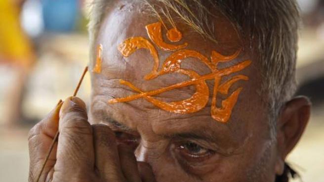 Un sacerdote pinta símbolos religiosos sobre la frente de un anciano devoto hindú durante el mes santo de Shravan, en una ciudad del norte de India.