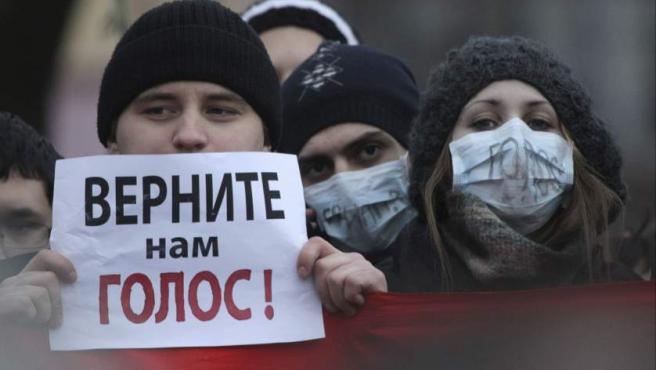 """Un hombre sostiene un cartel en el que se puede leer """"devuélvanos la voz"""", en una de las protestas en San Petersburgo contra el fraude electoral y Vladimir Putin."""