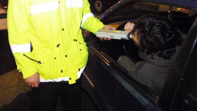 Un agente realiza un control de alcoholemia en una carretera.