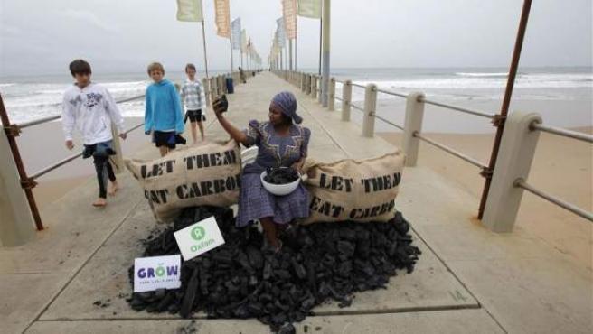 Una integrante de la ONG Oxfam en una protesta contra el uso de energía basada en combustibles fósiles en la playa de Durban (Sudáfrica).