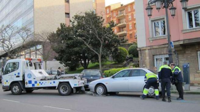 La grúa municipal retira un coche en Oviedo.