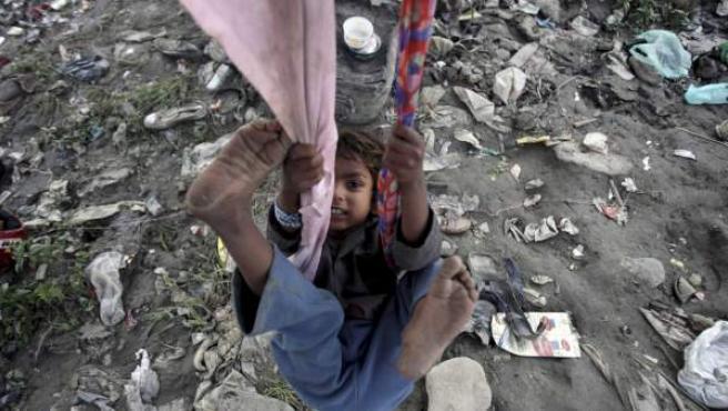 Un niño de un suburbio de Katmandú (Nepal) juega entre la basura debajo de un puente.