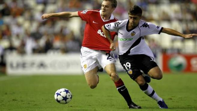 El centrocampista del Valencia CF, Pablo Hernández (d), lucha el balón con el centrocampista del Manchester United, Darren Fletcher.