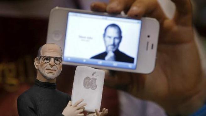 Un iPhone con la imagen de Steve Jobs tras una figura que representa al cofundador de la compañía.
