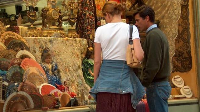 Dos personas observan el escaparate de una tienda.