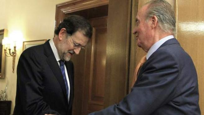 El rey Juan Carlos saluda al presidente del Partido Popular, Mariano Rajoy.