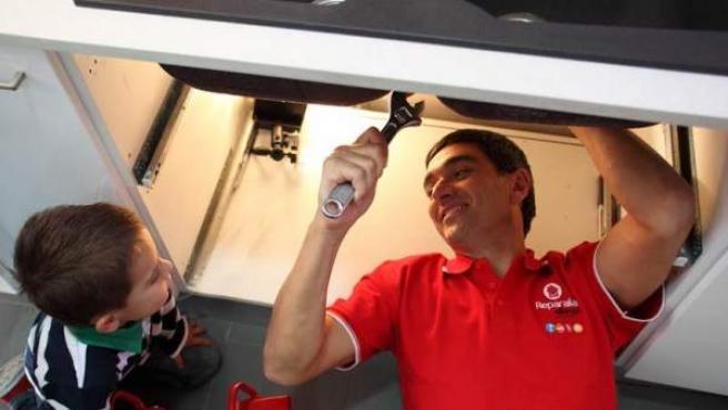 Un técnico arreglando el desagüe de la cocina.