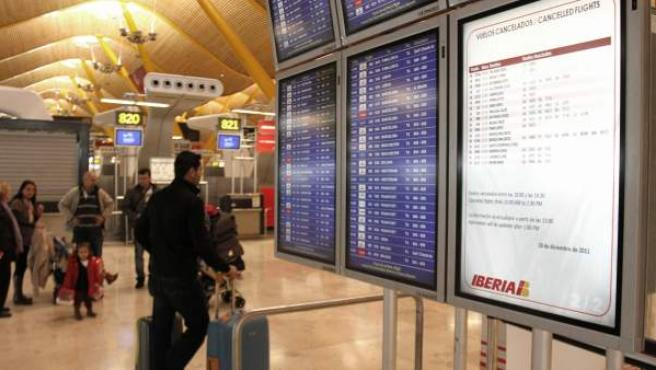 Un viajero observa en el aeropuerto de Madrid-Barajas un panel que anuncia vuelos cancelados de Iberia.