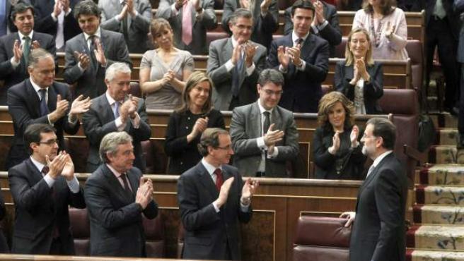 Los diputados populares aplauden a Mariano Rajoy tras su discurso en la primera sesión del debate.
