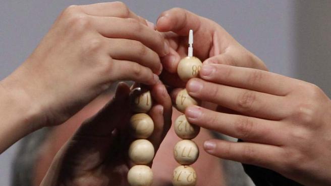 Las manos de los niños del colegio de San Ildefonso colocan en el alambre las primeras bolas de los números y los premios en el sorteo extraordinario de la Lotería de Navidad.