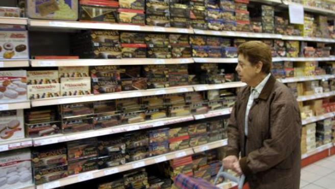 Una mujer observa una estantería llena de productos en un supermercado.