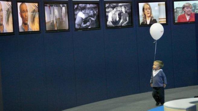 Un niño pasea con su globo por delante de varias pantallas de televisión.