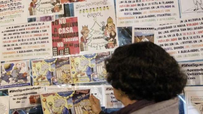 Una mujer lee los carteles reivindicativos que los manifestantes del 15M han colgado esta noche en la entrada del metro de Puerta del Sol.