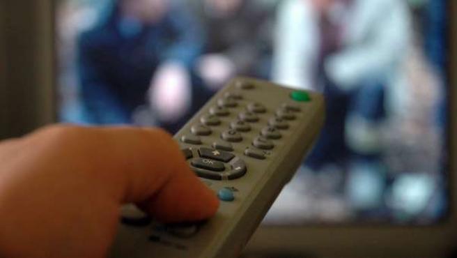 Un telespectador utilizando el mando a distancia del televisor.