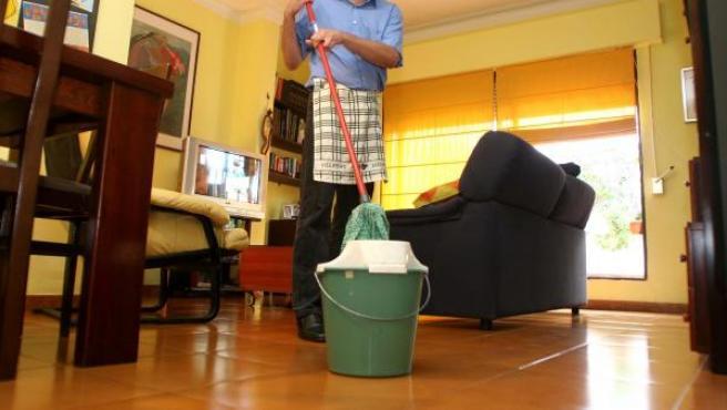 Un hombre realiza labores del hogar en su domicilio.