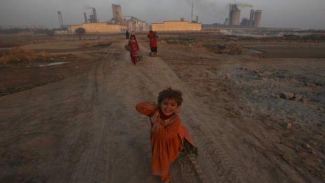Una niña corre por una carretera desierta en Pakarab, Pakistán.