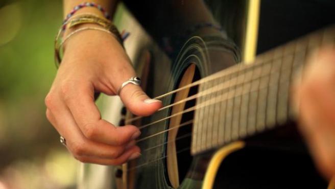 Una persona toca la guitarra.