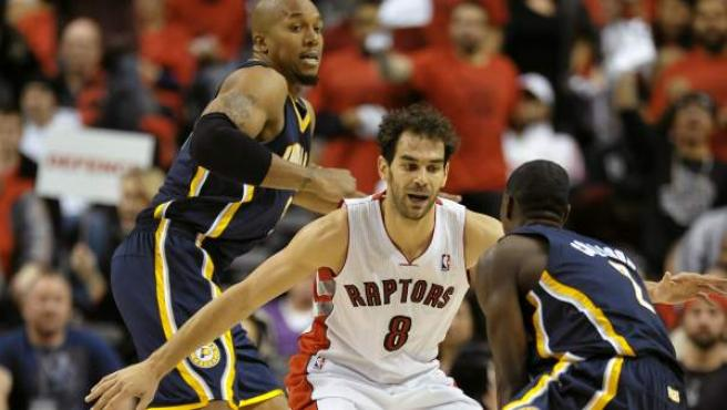 El jugador de los Raptors José Calderón (c) disputa el balón con David West (i) y Darren Collison (d) de los Pacers durante el juego de la NBA en Toronto (Canadá).