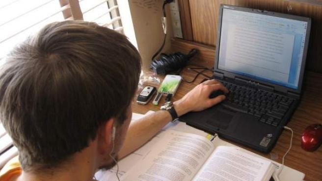 Un joven escribe en su ordenador portátil.