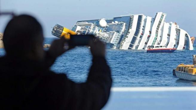 Un hombre saca una fotografía del crucero Costa Concordia, que encalló frente a las costas de la isla de Giglio, en Italia.