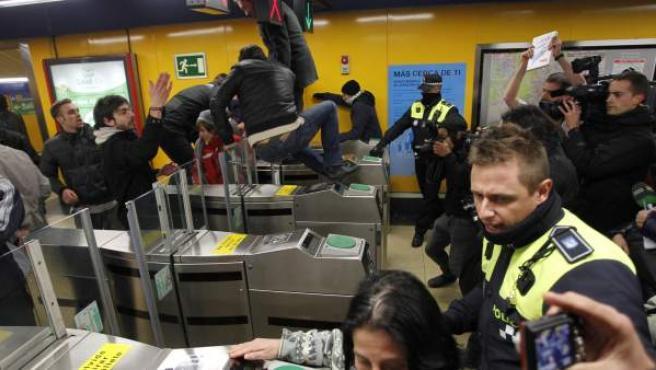 Varias personas se cuelan en la estación de Callao del metro de Madrid ante la atenta mirada de los policías municipales.