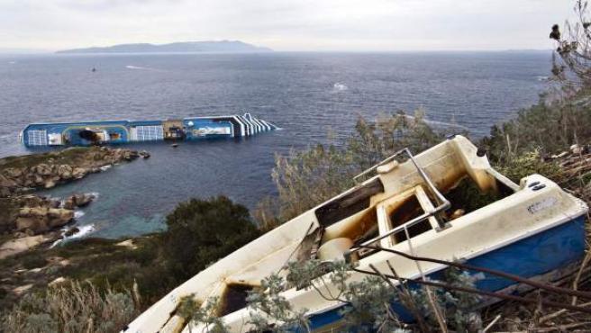 Vista del buque crucero Costa Concordia (izq, al fondo), que naufragó en aguas de la isla italiana de Giglio al chocar contra unas rocas próximas a la costa.