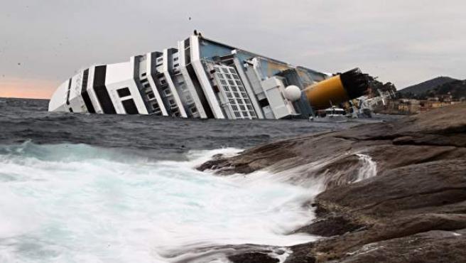 Las olas chocan contra las rocas cerca del buque crucero Costa Concordia.