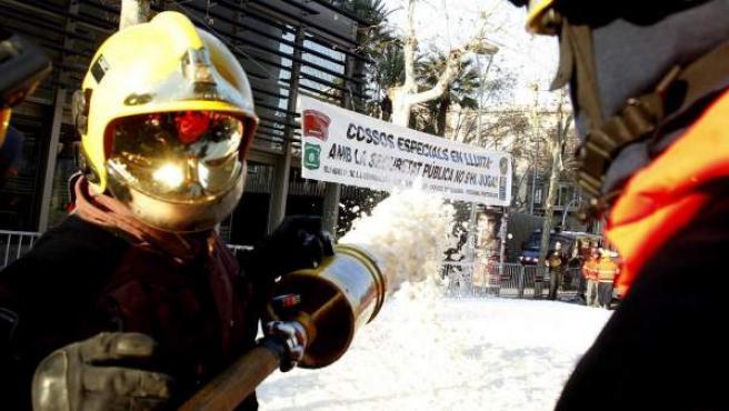 Medio centenar de bomberos de la Generalitat han protagonizando una sonora protesta ante la sede del Departamento de Interior y han cortado la circulación de la calle Diputación, que han inundado con espuma lanzada con un cañón manual.