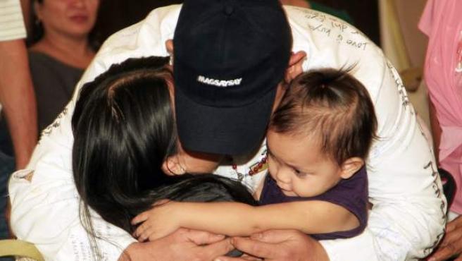 El filipino Rogelio Barsita, tripulante del Costa Concordia, abraza a su mujer y su hija a su llegada al aeropuerto de Manila (Filipinas).