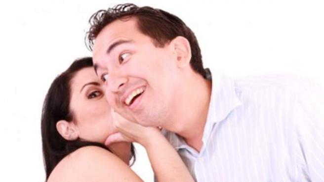 Dos personas, contándose chismes al oído.